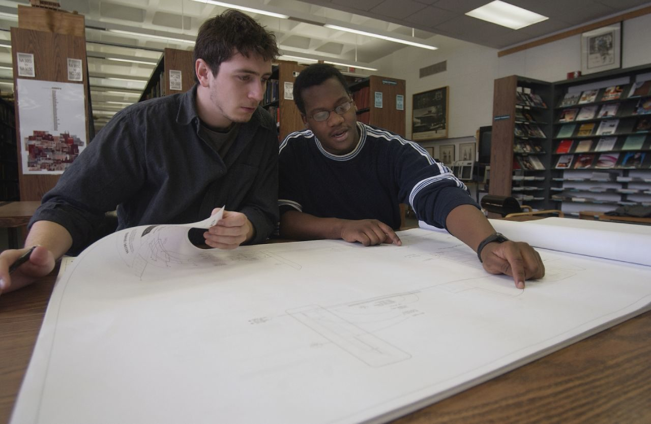 Male students studying a blueprint.