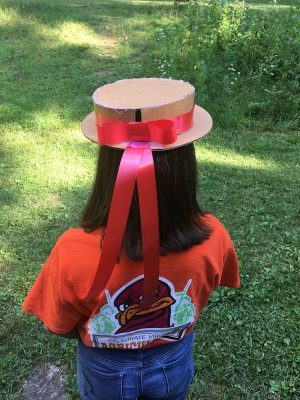 A round hat made of cardboard with a red ribbon tied around it. The hat is worn in a garden.