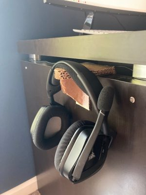 A headphone holder made of cardboard holding a pair of headphones. The holder is made to hang on the side of a desk.