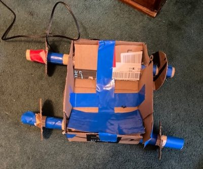 A vehicle made out of cardboard, blue tape, red tape, and some wire sitting on a carpeted floor.