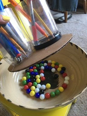 A lazy Susan style spinning plate with two cups hot glued on the top of a cardboard disc. The disc sits in a bowl filled with marbles and the marble allow the disc to be spun around.