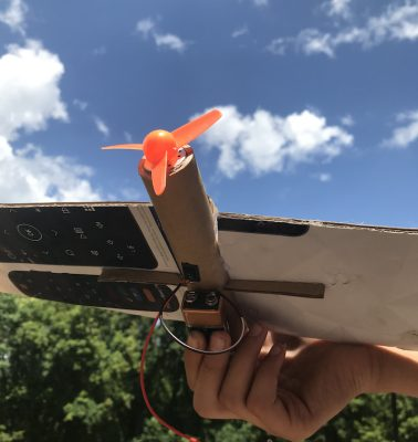 An airplane made out of cardboard with an orange propellor on a motor with a battery attached on the bottom of the plane.