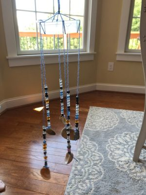 A wind chime made from a piece of plastic, yarn, beads, and seashells.