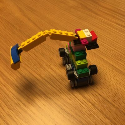 A car made out of legos that rolls on wheels and has an arm that bends.