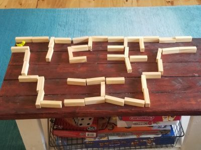 a maze made out of jenga pieces sitting on their sides on top of a wooden table