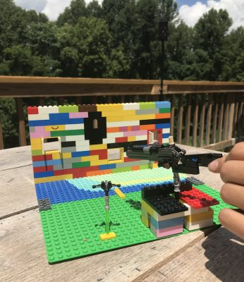 A shooting gallery made out of legos sitting on an outside table