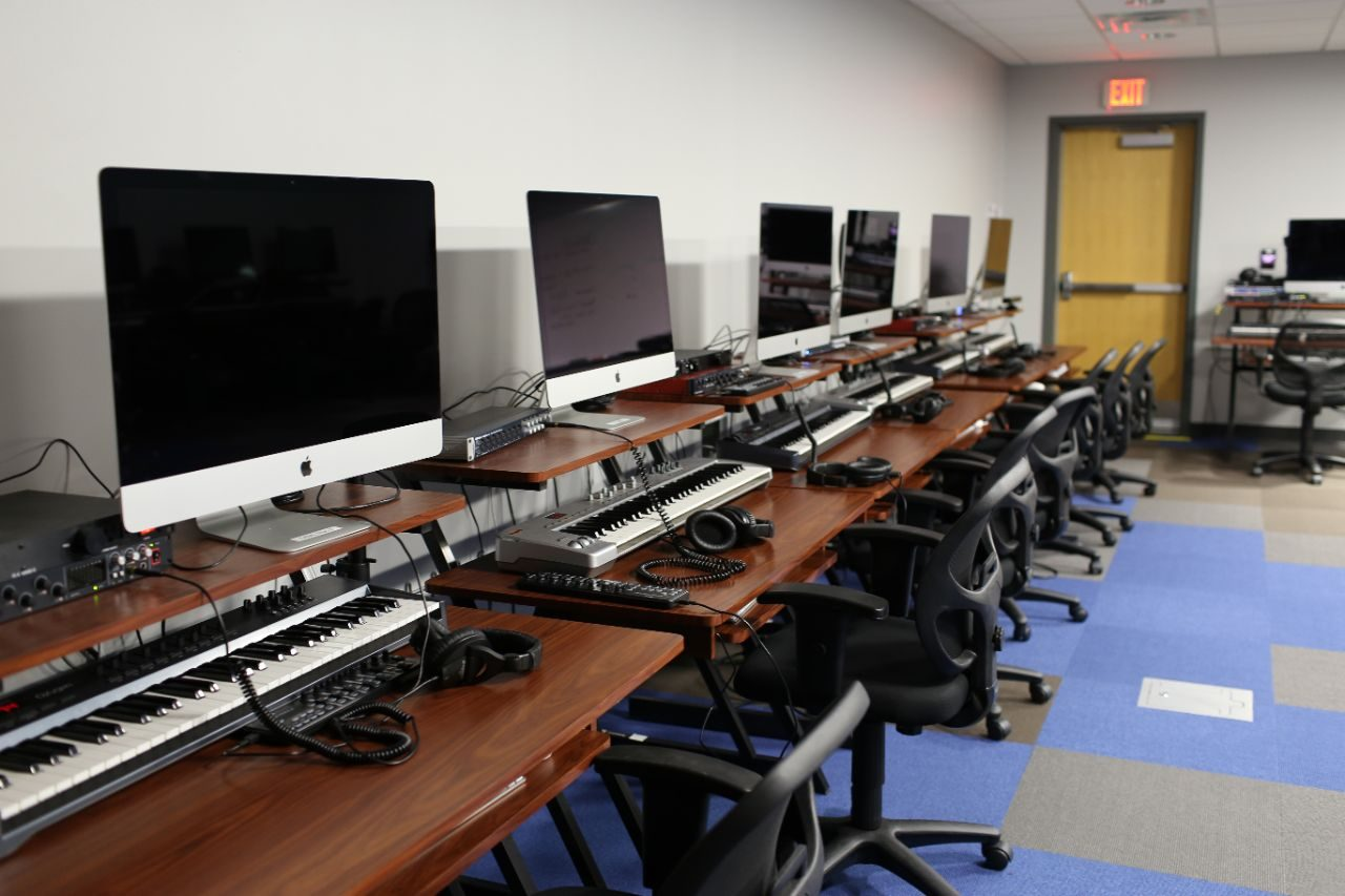 A row of iMac computers with keyboards and headphones at each station.