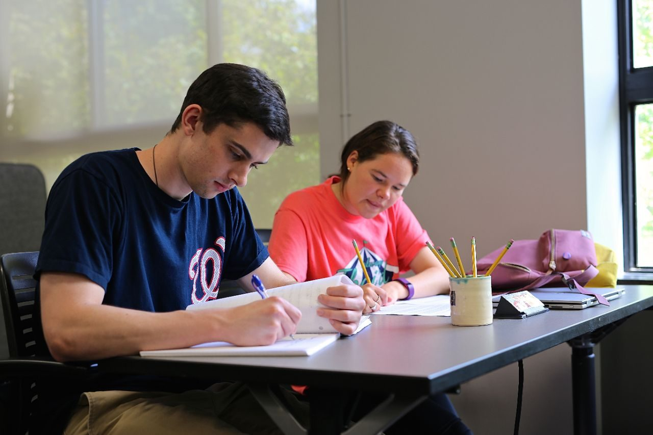 Students at a desk in the Writing Center