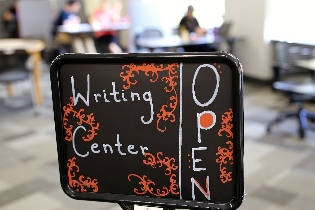 "Sign with ""Writing Center Open"" written in white and orange marker."