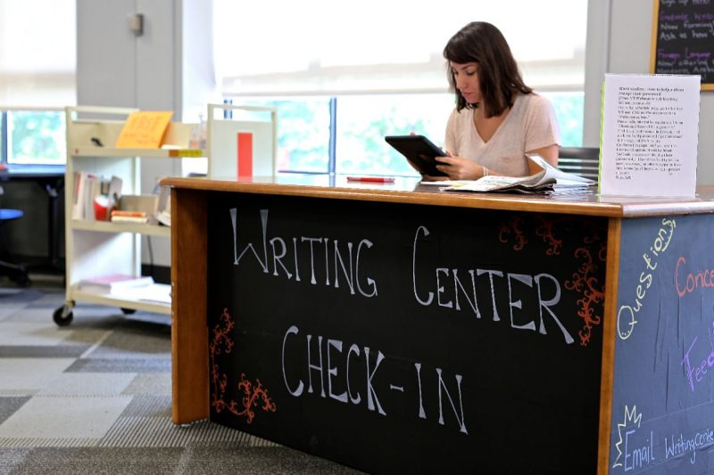 Writing Center Check in table with a woman sitting behind the desk.